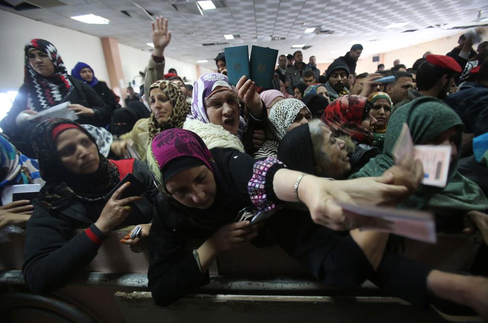 Donne palestinesi mostrano i passaporti a Rafah per oltrepassare il confine e andare in Egitto. - Ibraheem Abu Mustafa, Reuters/Contrasto
