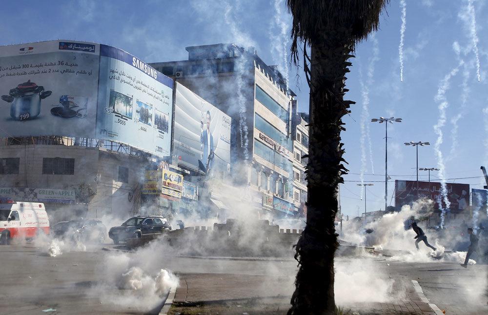 Palestinesi scappano dai lacrimogeni sparati dall'esercito israeliano a Hebron, in Cisgiordania, il 13 novembre 2015. - Mussa Qawasma, Reuters/Contrasto