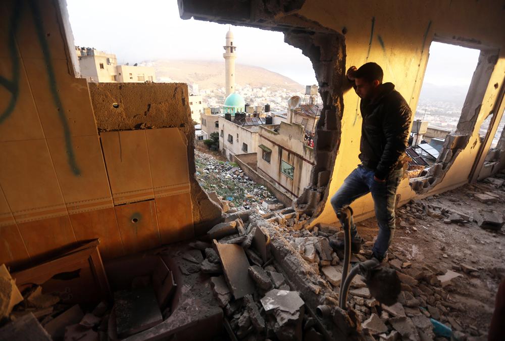 Un palestinese tra le macerie di una casa a Nablus, in Cisgiordania. A seguito degli scontri tra palestinesi e forze di sicurezza israeliane, le autorità israeliane hanno intensificato la demolizione delle case dei palestinesi.  - Jaafar Ashtiyeh, Afp