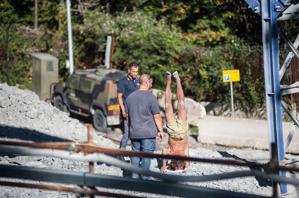 """Il pacifista Turi Vaccaro nel cantiere mentre fa """"la verticale"""" davanti ai funzionari di polizia, 5 settembre 2015. - Michele Lapini"""