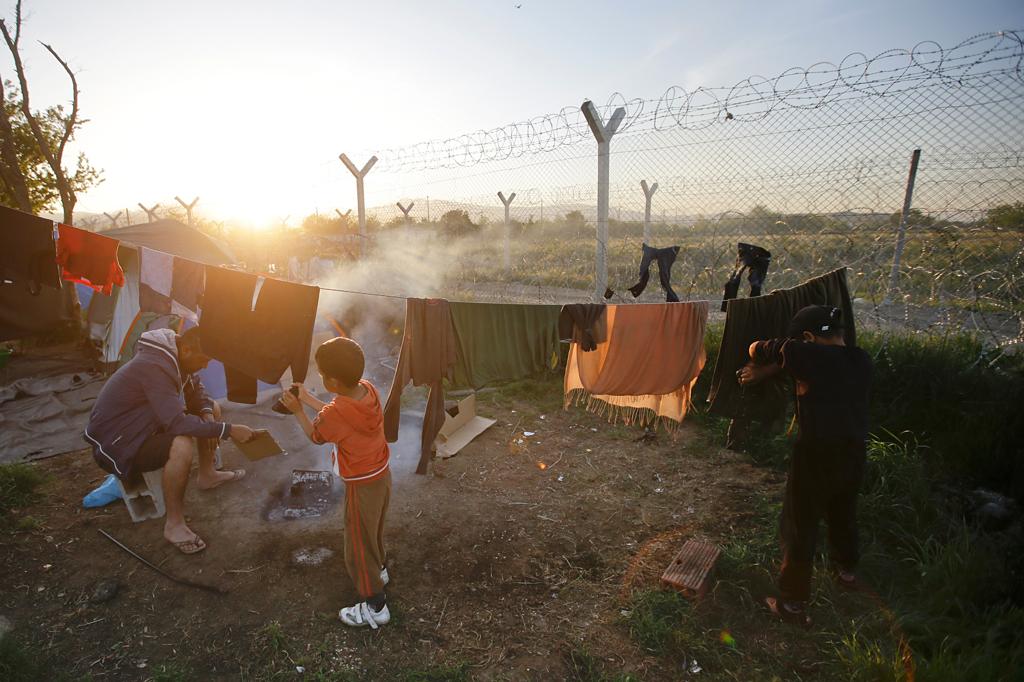 Sarab Al Jumaili, iracheno, con suo figlio Adnan, vicino alla recinzione che circonda il campo di Idomeni, il 22 aprile 2016. - Gregorio Borgia, Ap/Ansa