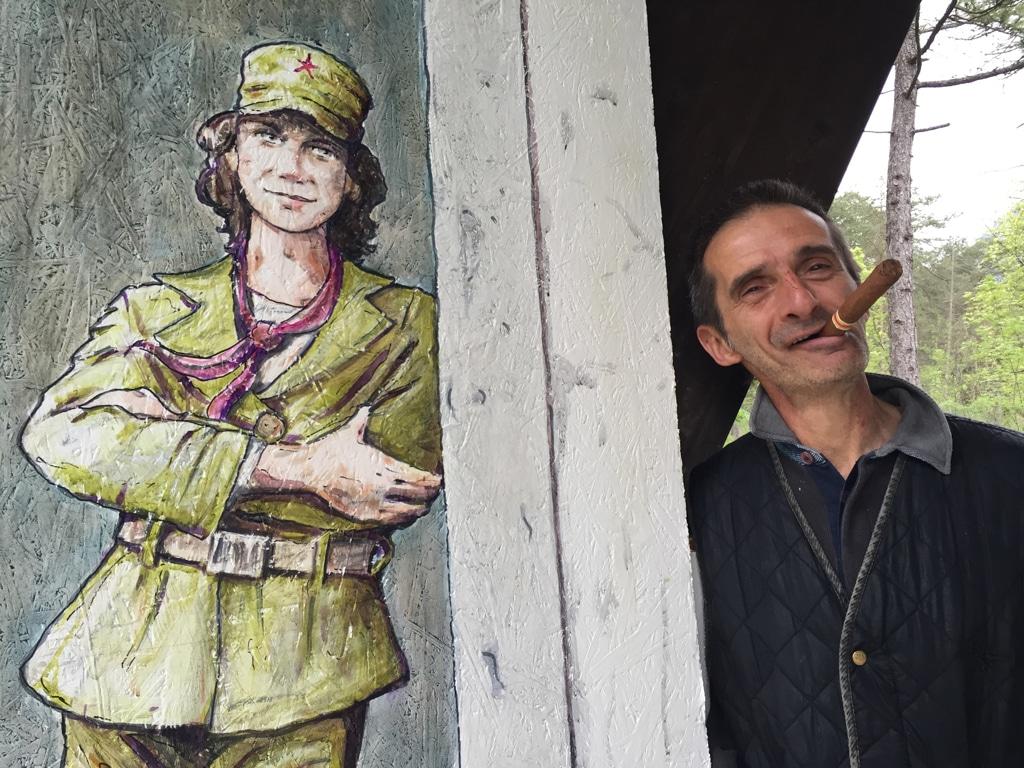 L'artista Guido Carrara posa accanto al murale che ricorda la combattente partigiana Jole de Cillia, a Tramonti di sotto. - Anna Lisa Soleti