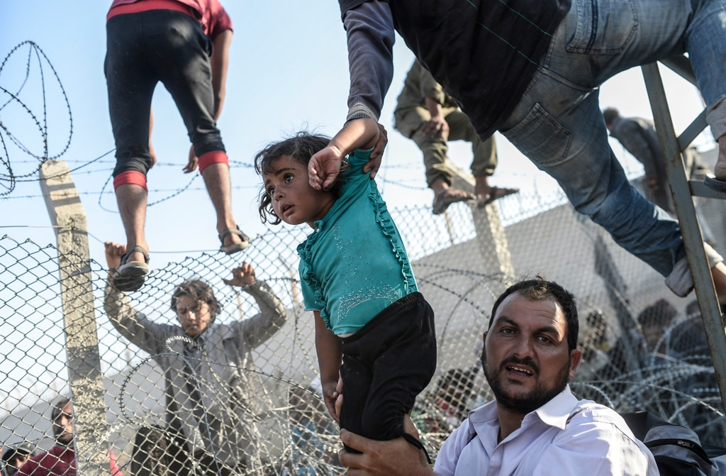 Famiglie siriane entrano in Turchia forzando la recinzione lungo il confine ad Akcakale, il 14 giugno 2015. - Bulent Kilic, Afp